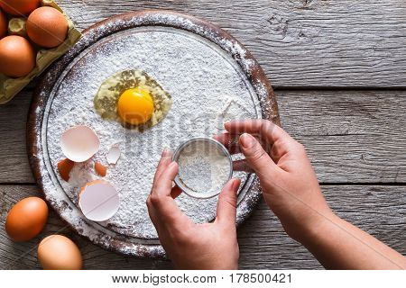 Baking concept. Yands sift sprinkled flour and eggs on wooden cutting board near knife, cooking ingredients. Prepare for making yeast dough. Top view, copy space