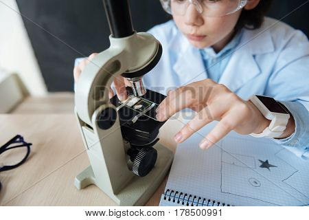 Exploring evolution of microbiology. Skillful gifted capable teenager sitting in the laboratory and enjoying science lesson while makig notes and using microscope