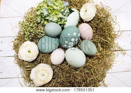 Close up with an easter nest on a white wooden table in vintage style