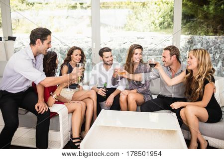 Group of friends talking to each other and cocktail drinks at party