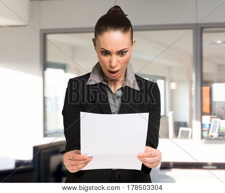 Surprised woman reading a business document in her office