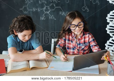 Using modern gadgets for education. Positive delighted little pupils sitting at school and enjoying class of foreign languages while making notes and using dictionary