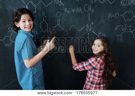Applying our knowledge . Capable brainy little pupils sitting at school and enjoying chemistry class while making notes on the blackboard and smiling