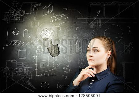 Thoughtful woman looking at bright bulb over icons on chalk board