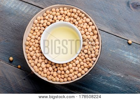 Soy beans and soy oil in bowls on wooden table