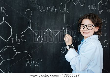 Showing my abilities. Delighted smart gifted pupil standing in the lab while enjoying chemistry class and making notes on the blackboard
