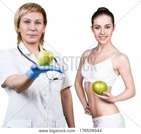 Doctor holds green apple. Young woman shows weight loss result. Healthy eating concept.