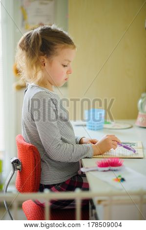 The schoolgirl of elementary school does homework. The girl sits at a school desk and with concentration reads. On table school supplies and different personal objects. To the child it is comfortable.