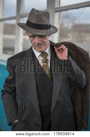 Vertical image of a mature man dressed as a 1940s gangster, posing for the camera