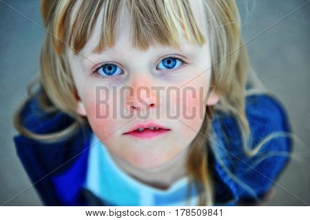 Portrait of a child with long blond hair and blue eyes wide open