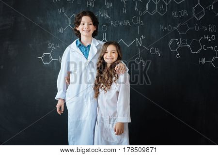 Waiting for practical assignments. Cheerful smiling friendly children standing near the blackboard in the laboratory while enjoying medicine class and hugging