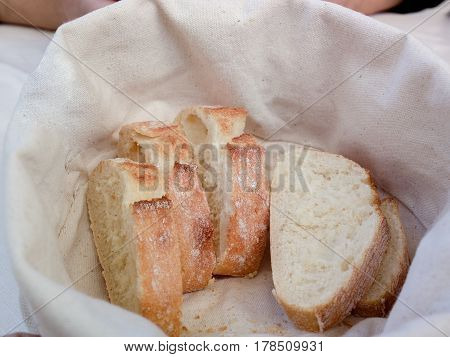 Slices of bread with Golden crust in white basket. Freshly baked and fragrant bread on table in restaurant. Italy.