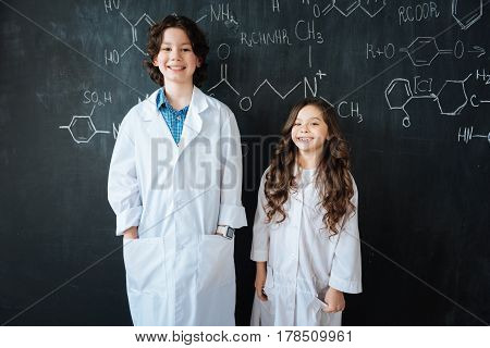 Friends in everything. Cheerful smiling friendly children standing near the blackboard in the laboratory while enjoying medicine class and hugging