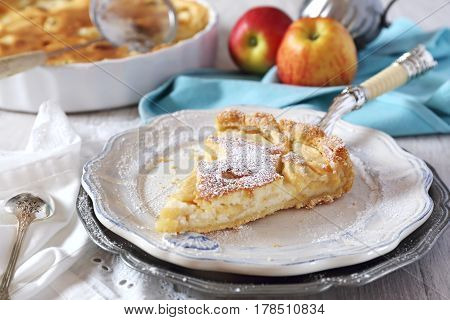 Apple tart with cream and two red apple, icing sugar dressing