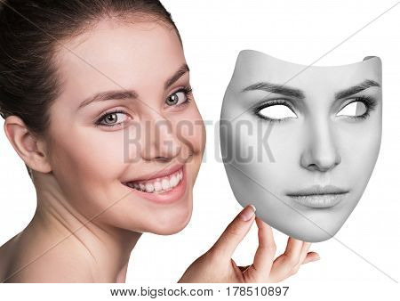 Young woman hiding hapyiness under the serious mask. Hypocritical, insincere, two-faced female