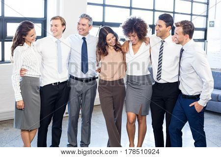 Businesspeople standing together with arms around each other in office