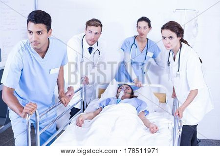 Concerned doctors standing near patient on bed in hospital