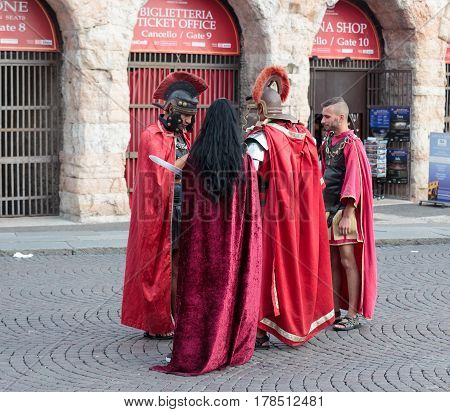Verona Italy September 27 2015 : Four people dressed in the form of Roman legionaries stand at the Piazza Bra square near the Arena in Verona Italy
