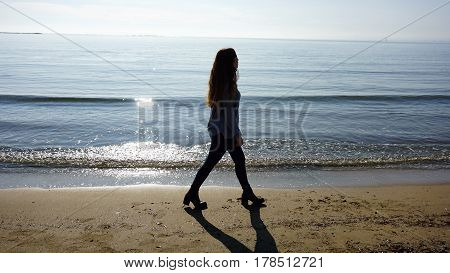 Gilr walking in the shore of a beach