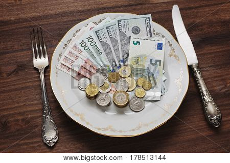 Different notes and coins including US dollars russian rubles euros and so on on the vintage plate with old silverware