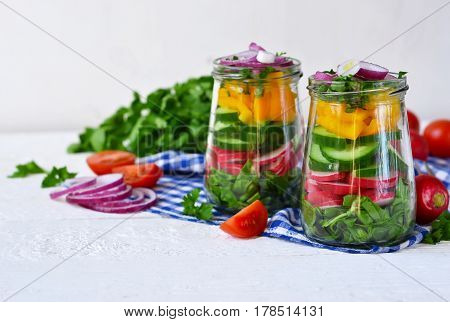 Vegetable salad with spinach and red onions in a glass jar on a white background