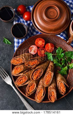 Pancakes made with liver stuffed with carrots and mushrooms on a black background