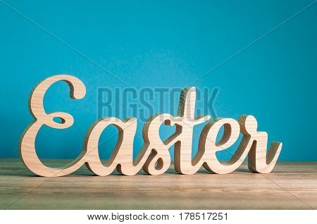 Easter - carved wooden text at blue background. Festive decoration. Happy Easter concept.