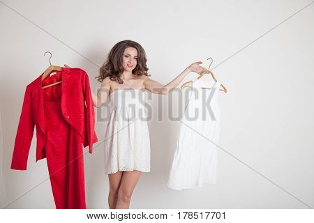 a girl chooses between red and white dress