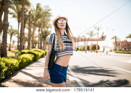 Travel Woman Hitchhiking. Beautiful Young Female Hitchhiker By The Road During Vacation Trip
