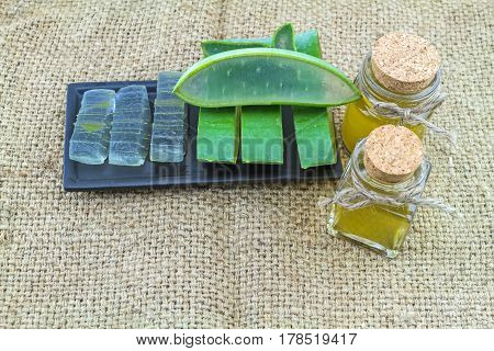 Fresh aloe vera gel on black ceramic dish with aloe vera essential oil and color pill on fabric sack