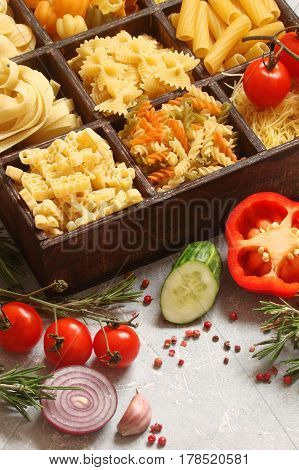 Pasta with vegetables spices and herbs in wooden box
