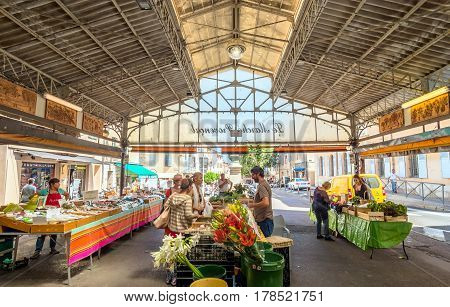 Antibes, France - June 29, 2016: day view of Cours Massena provencal market with tourists in Antibes France. Antibes is a popular seaside town in the heart of the Cote d'Azur.