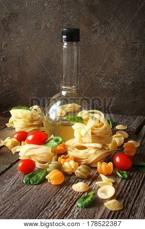 Italian pasta with olive oilvegetables and spinach on wooden boards in a rustic style