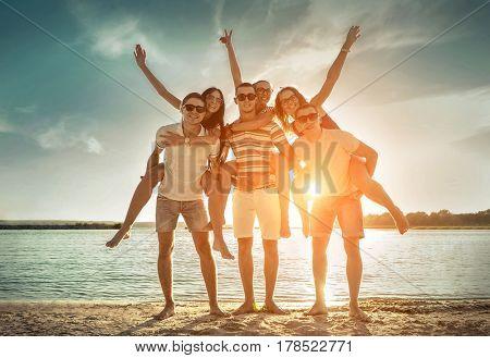 Friends fun on the beach under sunset sunlight at summer day.