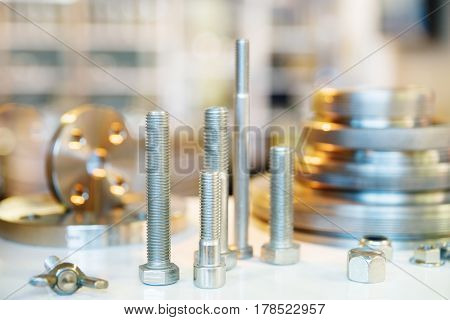 Metallic shape of flange gaskets and bolts. On a blurry background. Turning and milling industry. Metalworking. Horizontal close-up image.