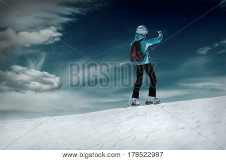 Woman stay on the ski and shoot selfie before sport action at sunny day around mountains under blue sky.