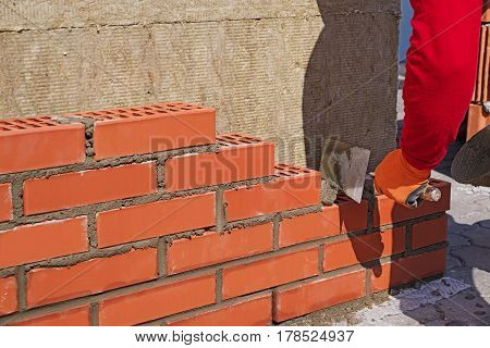 The Master With The Trowel Puts The Red Brick.