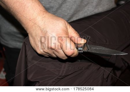 Closeup Of A Young Man Hand, Holding A Knife, About To Attack
