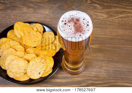 Lager beer in glass and potato chips on wooden background