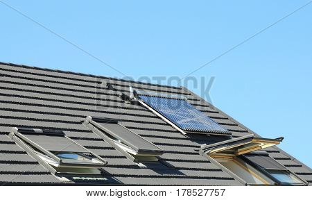 Modern House Roof with Solar Water Heater Solar Panels and Skylights Beautiful New Contemporary House with Solar Panels. Open attic skylights.