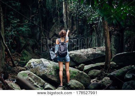 Back View Of Young Woman With Backpack In Tropical Jungle