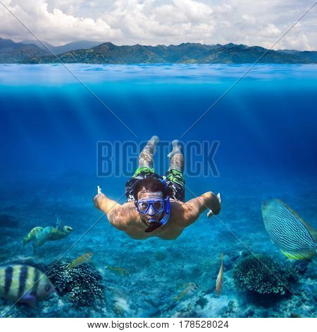 Underwater shoot of a young man snorkeling in a tropical sea on vacation. Design template