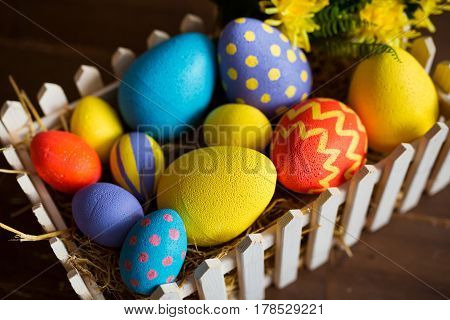 Colorful easter decorative eggs in wooden box.