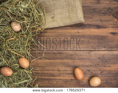 Rural eco background with brown chicken eggs, a piece of burlap and straw on the background of old wooden planks. The view from the top. Creative background for Easter cards, menu or advertising