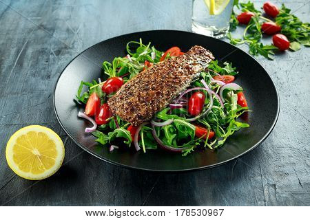Smoked Mackerel Salad with tomato, chopped red onion, Ruccola on black plate