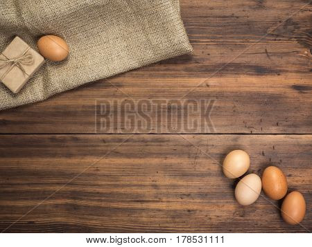 Brown chicken eggs and gift box lay on a piece of burlap on a wooden table from the old boards. Top view. Fresh chicken eggs close-up, background for advertising or Easter greetings, rustic style