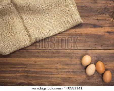 Brown chicken eggs lay on a piece of burlap on a wooden table from the old boards. Top view. Three fresh chicken eggs close-up, background for advertising or Easter greetings, rustic style