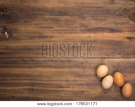 Easter eggs on old wooden table from planks. Top view with space for your design, Easter greetings or advertising. Rustic background.