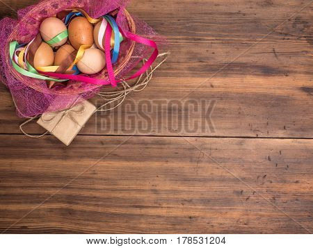 Easter eggs in the basket with colored ribbons on the background of wooden table from the old boards with gift boxes, top view. Background with in rustic style for advertising or Easter greetings