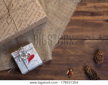 Vintage gift box, fir cones, Christmas toy on wood and burlap vintage background, photo top view. Copy space for text. Top view, Studio photography